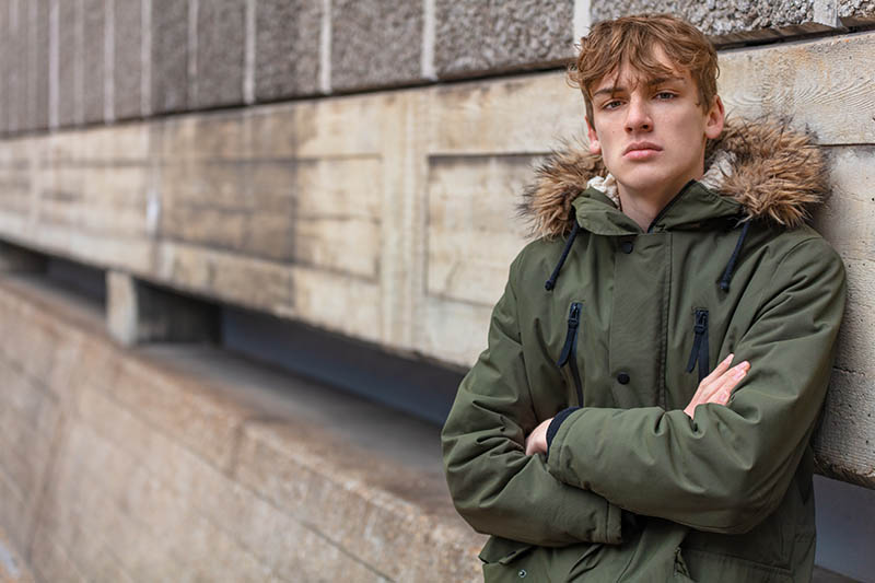 Young adult male teenager boy outside in an urban city wearing a green parka coat leaning against a wall